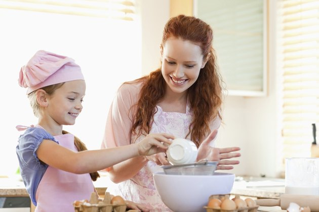 Smiling mother and daughter preparing dough