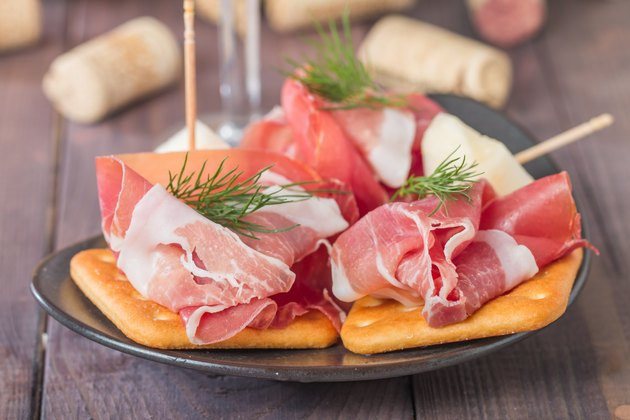 slices of cured ham with melon and red wine