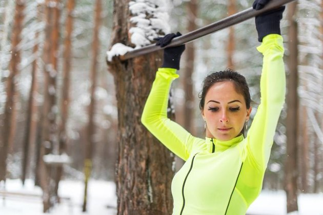 Fit woman athlete performing pull ups in a bar. Winter street outdoor training workout