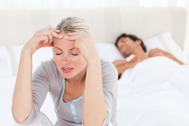 Attractive woman having a headache while her husband is sleeping