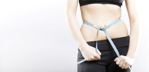 Woman measuring her waist, weight loss concept
