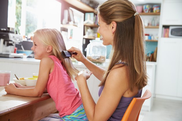 Mother Brushing Daughter's Hair At Breakfast Table