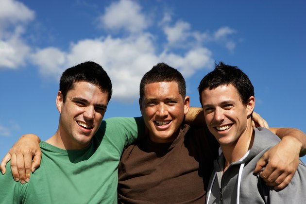 Three young men embracing outdoors, portrait, upper half