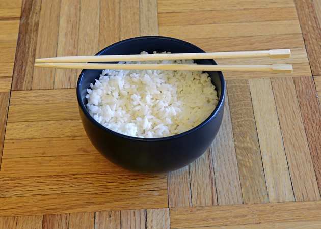 Bowl of white rice and chopsticks on wooden table