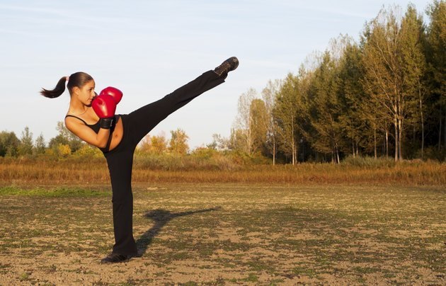 Kick boxing girl exercising in the nature