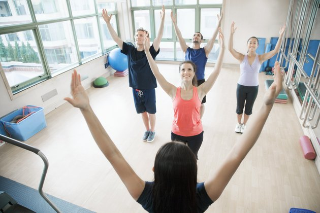 Young people with hands in the air in a yoga class