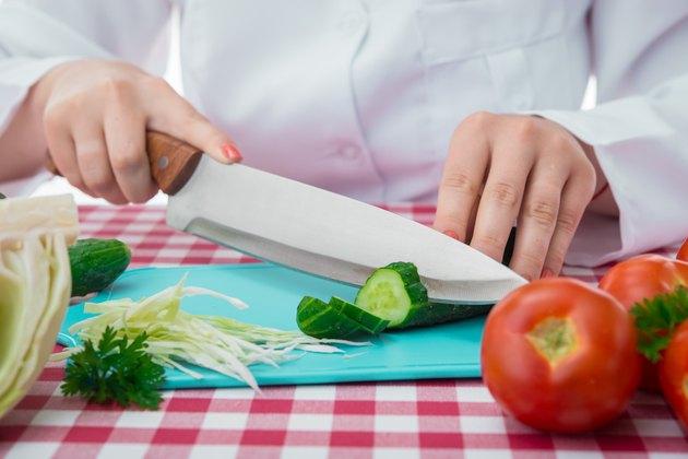 female cook slicing vegetables
