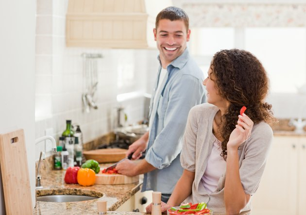 Beautiful woman looking at her husband who is cooking