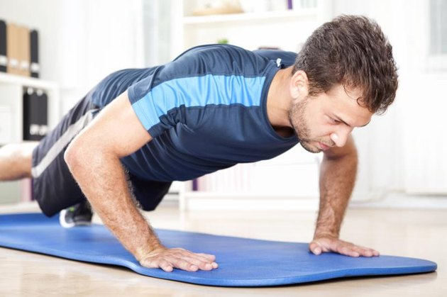 Fit Young Man Doing Indoor Planking Exercise on a Mat at Home, Showing Full Determination Expression.