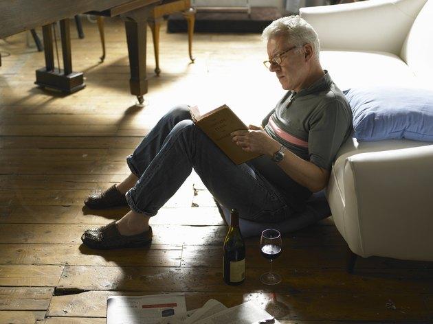 Mature man sitting on floor, reading