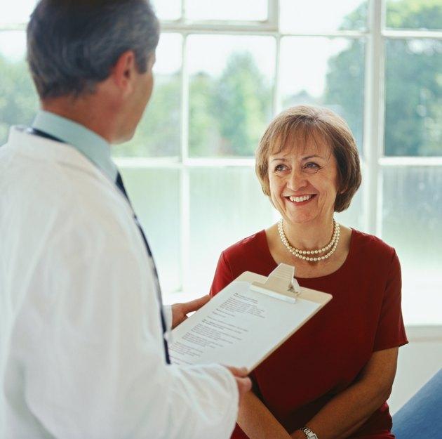 portrait of an elderly woman talking to a male doctor