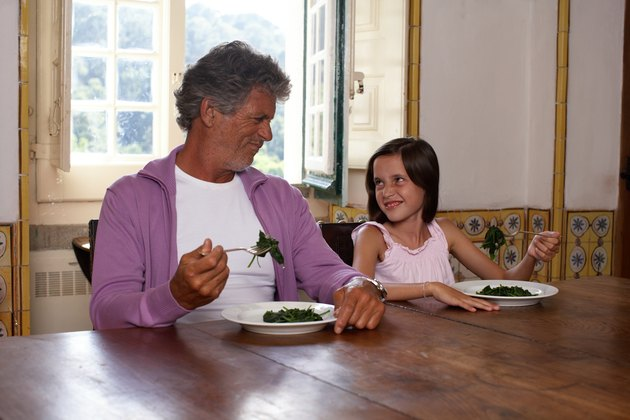 Father and daughter (10-11) sitting at table eating spinach