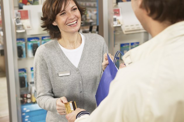 Man giving woman card at shop counter, smiling, close up