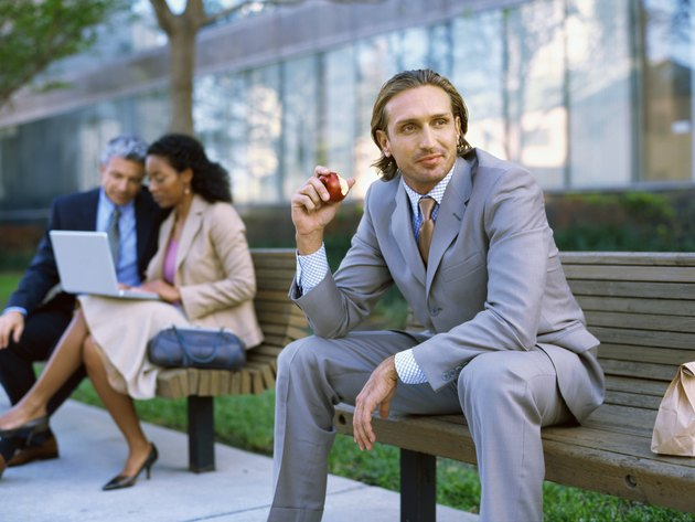 Side view of a businessman sitting on a bench and eating an apple
