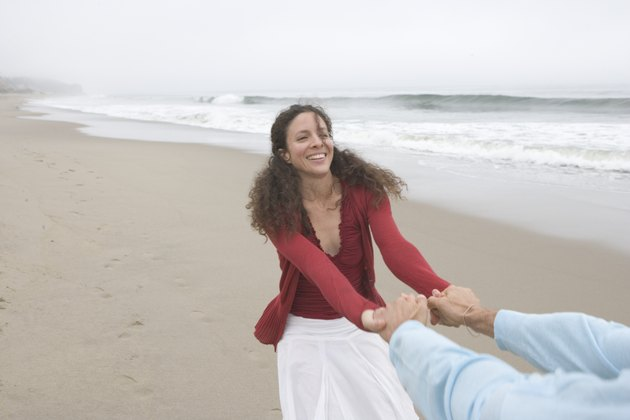 Woman pulling her boyfriend at the beach