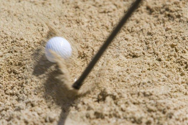 Golf club hitting ball on sand, blurred motion, Saipan, USA