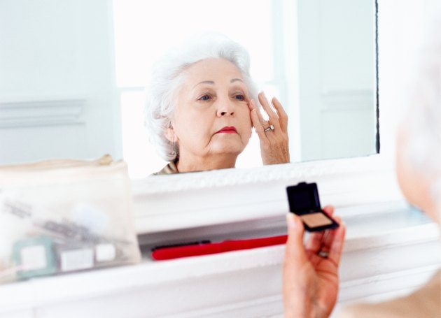 portrait of an elderly woman applying makeup