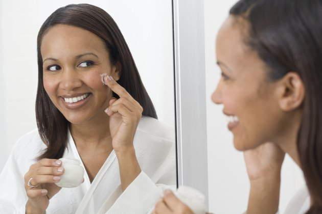 African woman applying face cream in mirror
