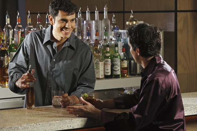 Hispanic male bartender talking to customer
