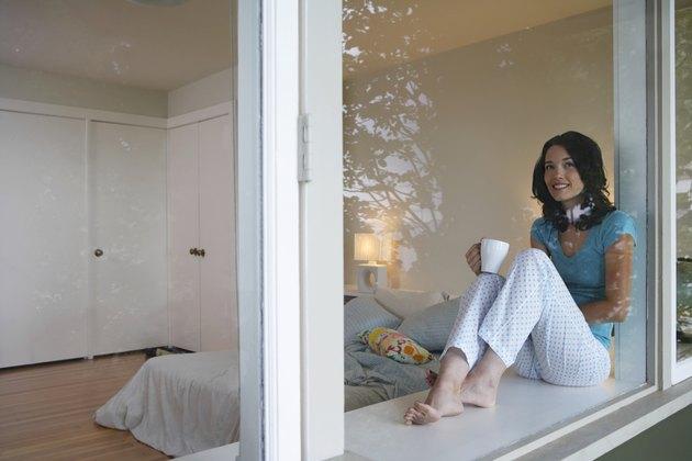 Woman sitting on windows sill, drinking coffee, smiling