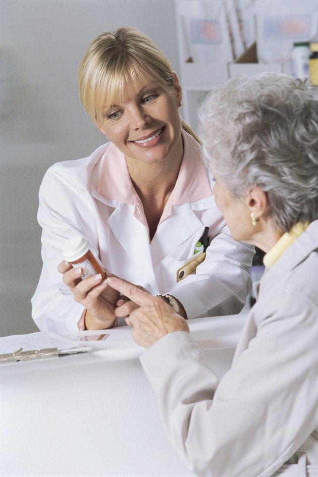 Woman and pharmacist looking at bottle of prescription medicine