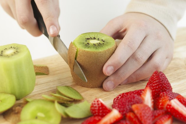 Removing the skin of a kiwi fruit, close up