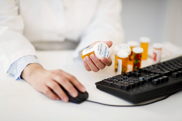 Pharmacist with pill bottles at computer