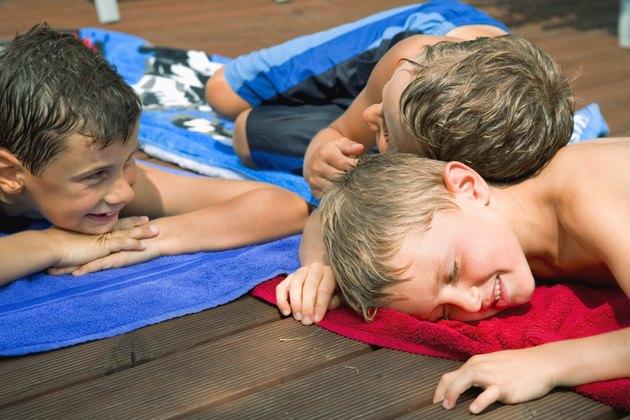 Boys lying on towels