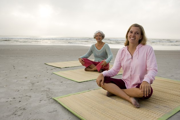 Mother exercising with daughter on a mat at the beach