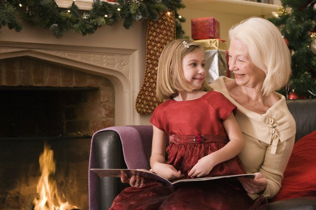 Grandmother and girl reading book at Christmas