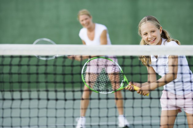 Girl playing tennis with parent
