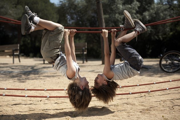 twins hang from structure in park
