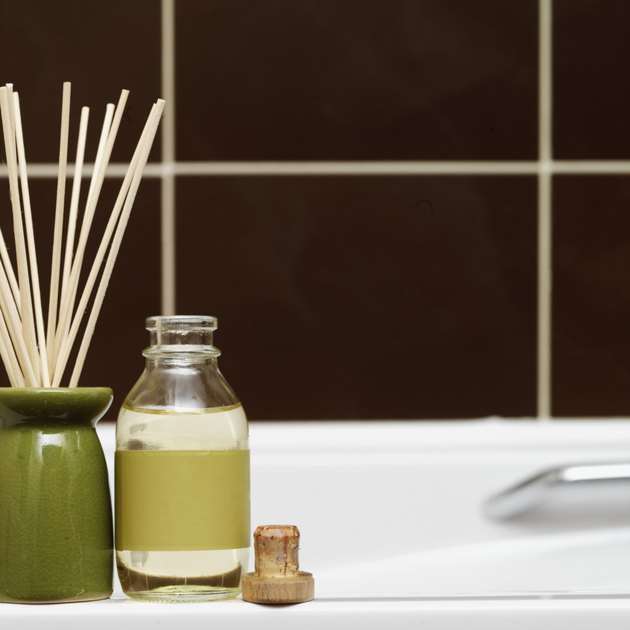 Close-up of incense sticks in a burner with a bottle of oil on side of bathtub