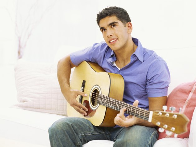 close-up of a young man sitting on a sofa and playing a guitar