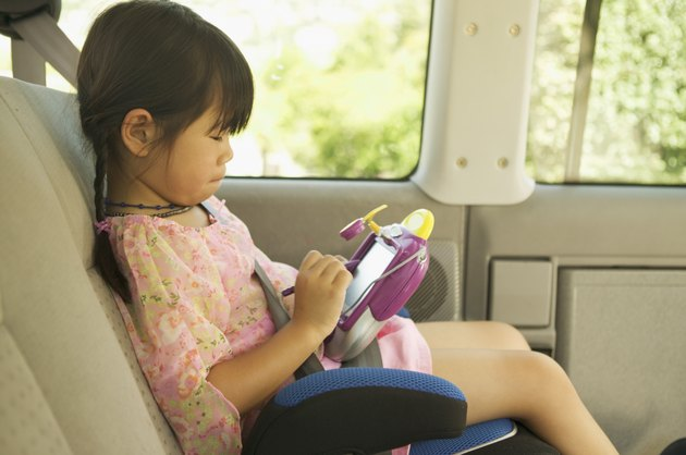 A girl in her car seat playing with an electronic toy