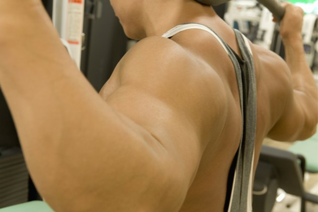 Man doing exercise with machine in gym, side view, differential focus