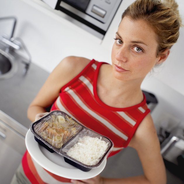 portrait of a young woman holding a cooked microwave dinner