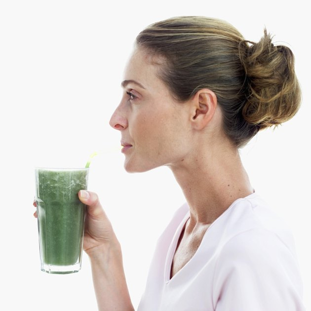 side view of a woman drinking a glass of thick green vegetable juice with a straw