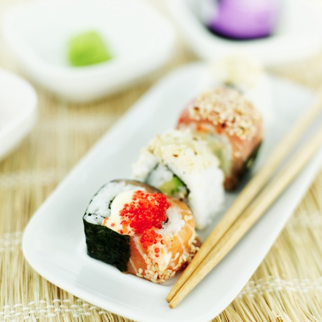 close-up of a tray of assorted sushi rolls served with chopsticks