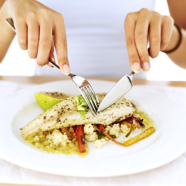 close-up of a woman's hands cutting a portion of food