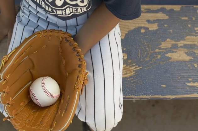 High angle view of a young boy wearing a baseball mitt holding a ball