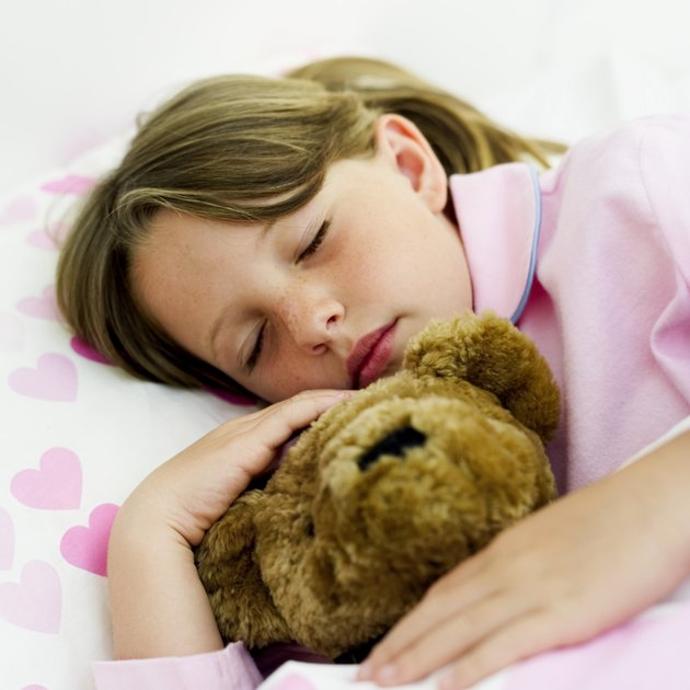 girl (6-7) asleep with teddy bear