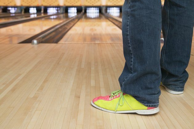 Low section view of a young person standing in a bowling alley