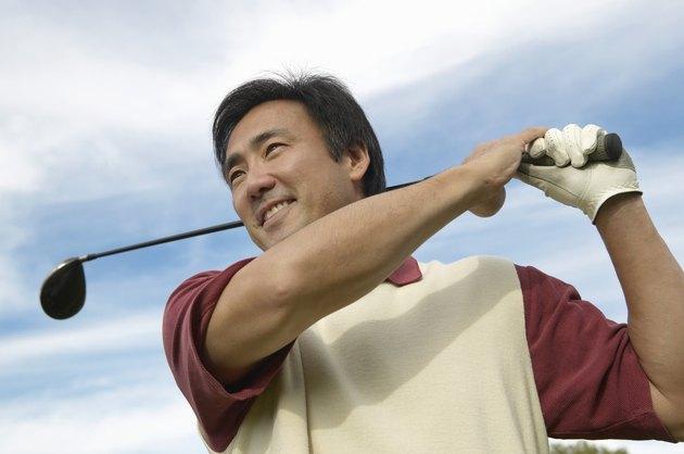 Smiling Man Swinging a Golf Club