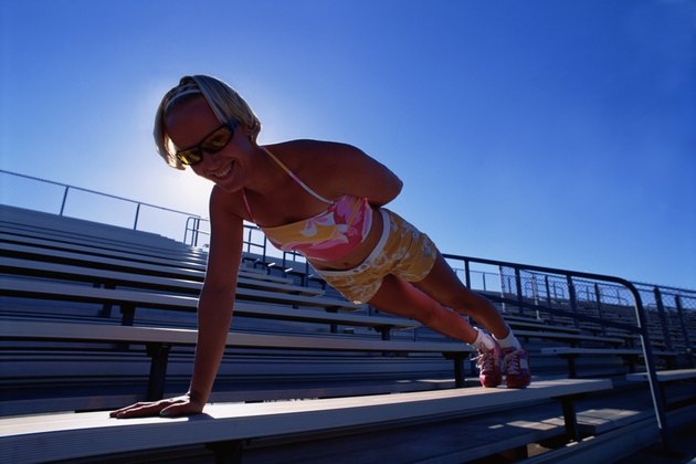 Young woman doing one armed push up on bleacher