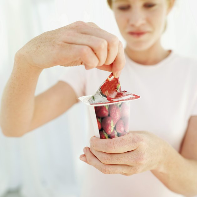 Woman opening a strawberry yoghurt