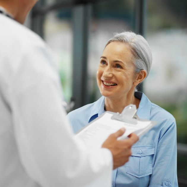 Close-up of doctor talking to mature patient while holding clipboard