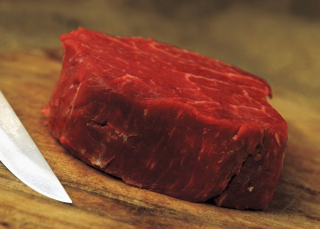 a piece of red meat with a knife