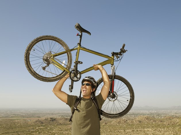 Hispanic man holding bicycle over head