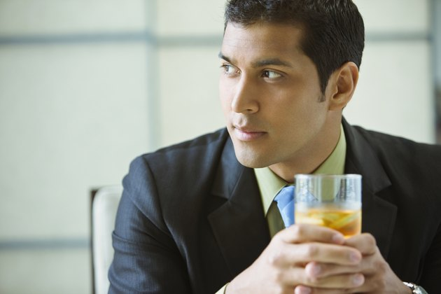Hispanic businessman drinking mixed drink